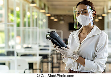 Waitress with face mask hold credit card reader. - Portrait ...