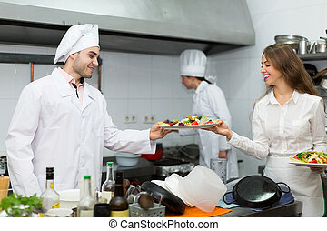Waitress with food at kitchen