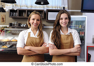Waitresses working at a cafe - Two happy waitresses working...