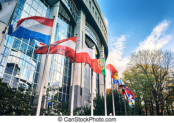 Waiving flags in front of European Parliament building. Brussels