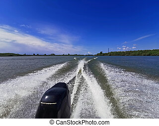 Wake leads water behind speeding boat