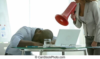 African-American businessman sleeping in the middle of the day, woman coming with a megaphone to wake him up