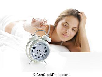 Wake up - Woman turning off the alarm clock