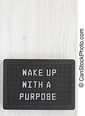 'Wake up with a purpose' words on a black lightbox on a white wooden background, top view. From above, overhead, flat lay. Copy space.