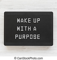 'Wake up with a purpose' words on a black lightbox on a white wooden background, top view. From above, overhead, flat lay.