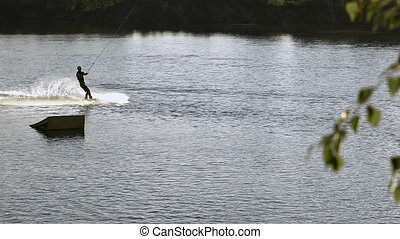 Wakeboarder making tricks on sunset. Extreme water sports...
