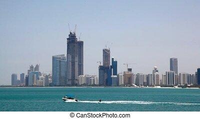 wakeboarding on sea against skyscrapers on seashore in Abu Dhabi, UAE