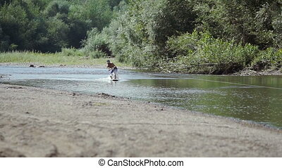Wakeboarding on the river - A man practicing wakeboard on...