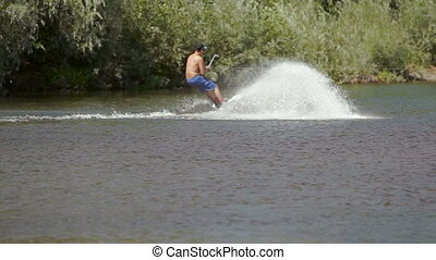 Wakeboarding on the river with action camera. - A man...