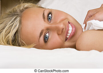 Waking Up To Beauty - A beautiful young woman laying in bed...