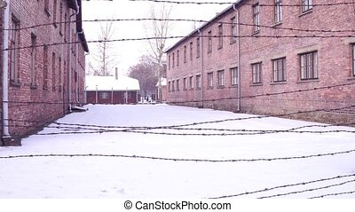 Walk along old barbed wire fence of Auschwitz Birkenau concentration and extermination camp. Brick barracks in winter. 4K video