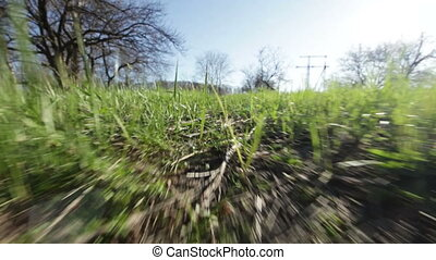 Camera moves along the path towards the sun through the spring the young grass in the industrial zone