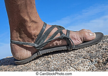 Closeup of man's weathered foot in rustic leather sandal stepping on rock high up on mountain with blue sky in background