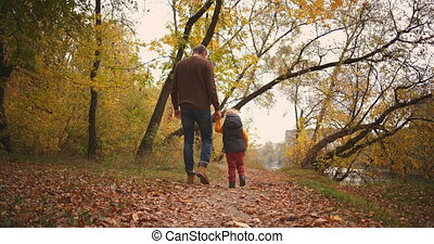 walk of father and son in autumn forest, man and boy are holding hands and moving on pathway between yellowed trees, stepping on dry foliage on ground, rear view