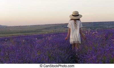 Walk of the girl on the lavender field at sunset in slow motion