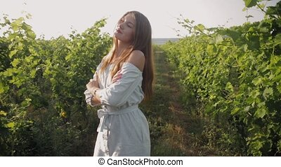 Walk of young beautiful woman in the ranks of vineyard