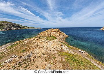 Pietra Islet Coastline landscape of Ile-Rousse city in Corsica, Red Porphyry rocks texture is at foreground, Haute-Corse, France