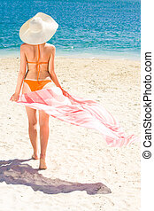 Portrait of woman with pareo walking aback along sandy beach during vacation