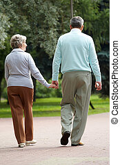 Walk - Rear view of senior couple walking down in park and ...