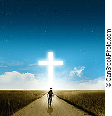 A man walking towards a large glowing Christian cross