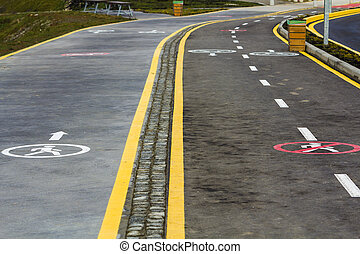 Walk way and bicycle lane signs on the asphalt road surface