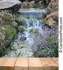 Walk way in beautiful garden with small waterfall