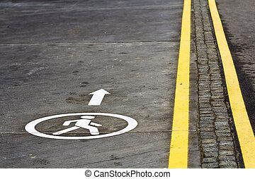 Walk way sign on the asphalt road surface