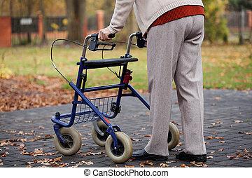 Walker - Disabled elder person walking with walker