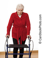 Walker - Elder disabled woman is walking with walker