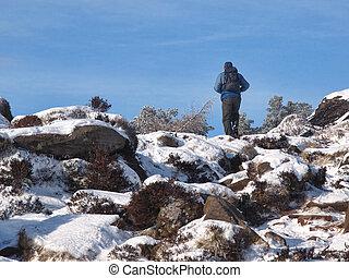 Walker on rocky snowy hill