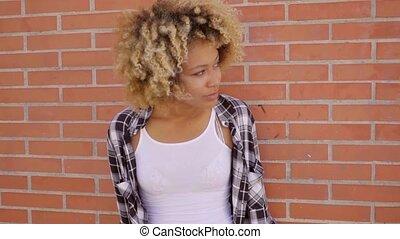 Walking Along A Brick Wall - Young mixed-race attractive...