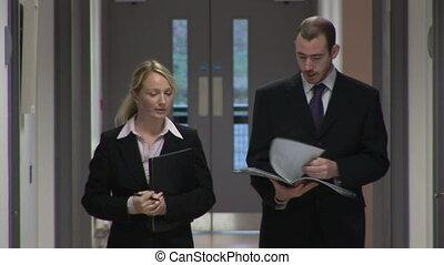 Walking along a Corridor - A business man and woman walk...