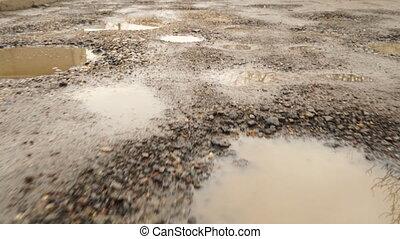 Walking along bad broken road with holes and muddy puddles....