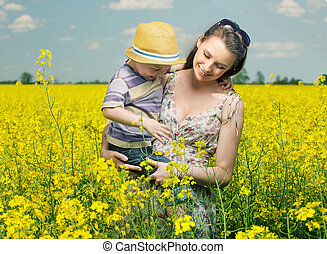 Walking among the canola flowers - Mother and son walking...