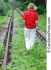 Walking Away Along Abandoned Railroad Track - Caucasian lady...