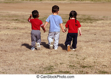 Three siblings walking away. I took this picture of my kids walking away from me at the park.