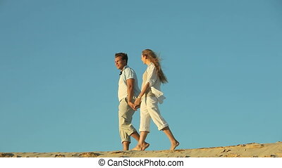 Barefoot couple enjoying an evening walk along the beach