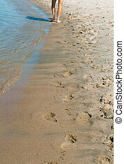 walking barefoot on the beach, human footprints in the sand