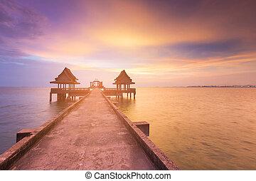 Walking boardwalk leading to ocean sunset skyline