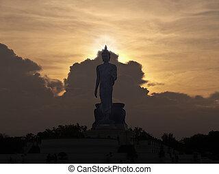 Walking Buddha image in Vitarka Mudra posture at twilight...