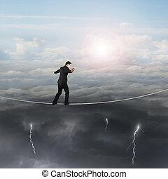 Walking businessman balancing on rope with sun sky cloudy lightning