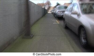 Blurry hand held walk down an urban sidewalk