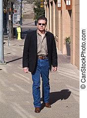 Walking Downtown - A man walking on a city sidewalk on a...