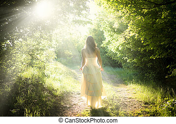 Beautiful young woman wearing elegant white dress walking on a forest path with rays of sunlight beaming through the leaves of the trees