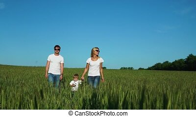 Walking family in the field with one child in white...
