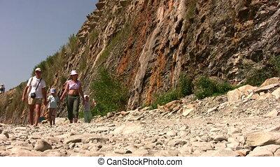 walking family on stone beach