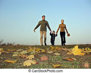 walking family sundown autumn leaves