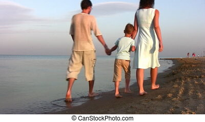 Walking family with boy on beach