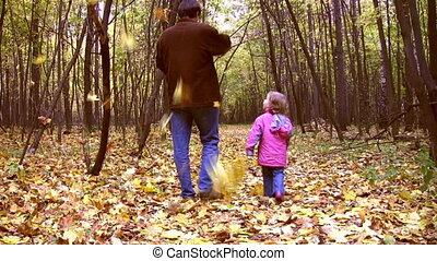 walking father with little girl in autumn park