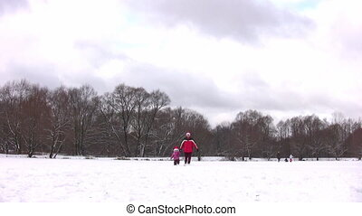 walking father with little girl on winter pond